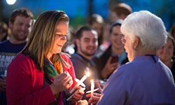 Reunion attendees and students light candles at the alumni induction ceremony